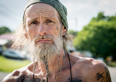 Portrait of a man with a grey braided beard and a headscarf. Many tattoos like a tear tattoo on his cheek. Ellis Travel photography