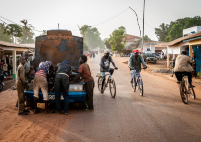 Car mechanics working on a car in the streets of Gabu, Guinee Bissau. Ellis work Photography