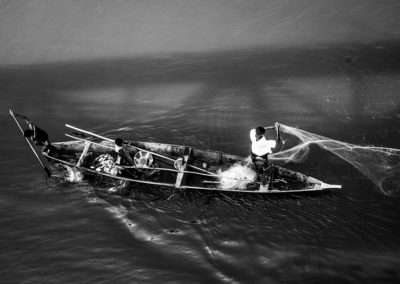 Black and white photo of fisherman in Kouroussa, Guinea Conakry. Picture is taken from above showing a wooden boat and a net being thrown away.