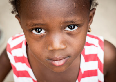 Close up of a girl form the Gambia. Looking straight into the camera with her big eyes. Sweet, cute girl. Ellis Kids Photography.