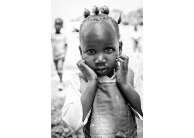 Black and white portrait of a girl from Gambia. Looking shy into the camera, with both hands on her cheeks. Ellis Photography