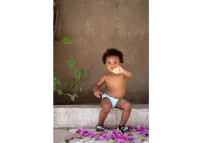 Cute little girl sitting with an orange in her hand. Pink flowers on the floor, plain wall and some green leaves. Kids photography by Ellis