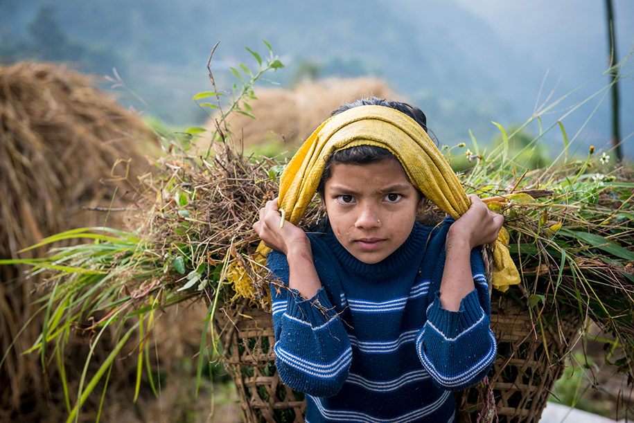 Girl from Nepal at work. caring a big basket on her back. Scarfs are visible on her face and arms. Kids photography by Ellis Peeters