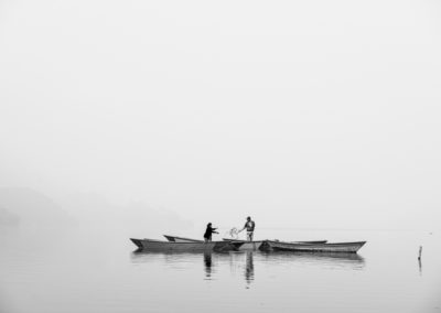 Black and white photo of a man and wife or are working and fishing in the lake of Pokhara. It is very foggy, so everything disappears, except for the boat and the fishers. Travel Photography Ellis