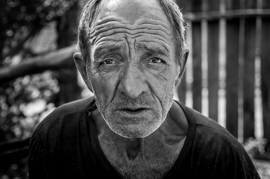 Black and white portrait of an older Romanian man, looking straight into the camera. Deep wrinkles from the sun and age.