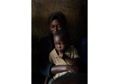 African lady with a child on her lap. Sitting in a dark living room.