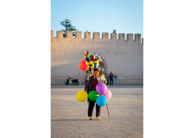 A photo of a man selling bright coloured balloons at the square of Essouira, Morocco. Behind him is an old wall visible. Travel photogrpahy