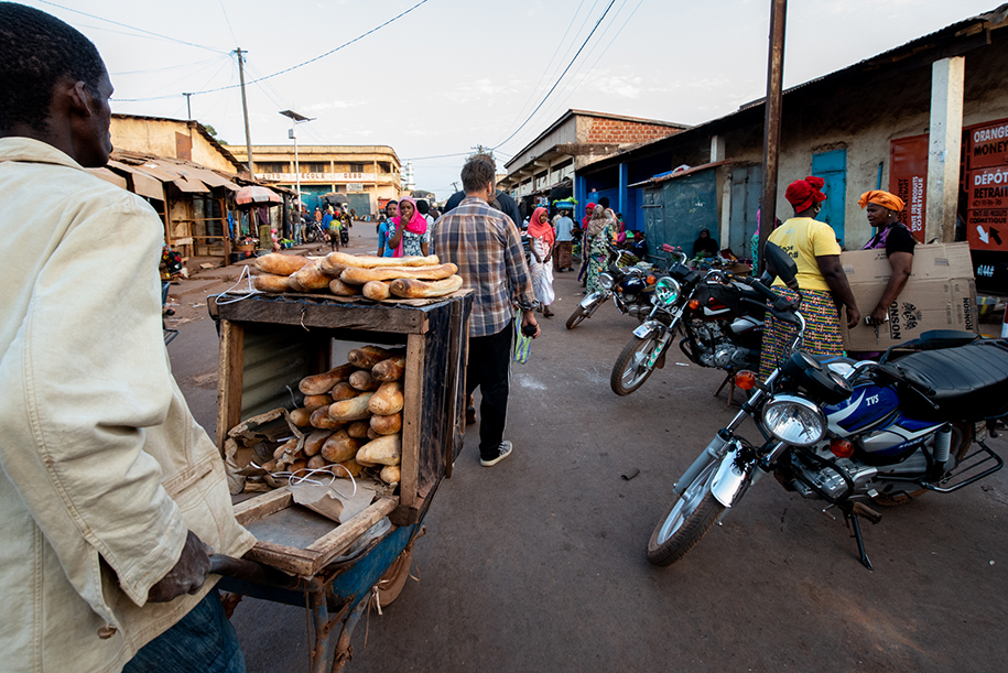 A baguette seller passing with is wheelbarrow full of baguettes in the streets of Labé, Guinee Bissau. Travel work photography.