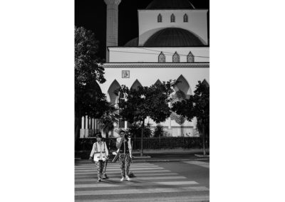 Black and white work photo of two cleaning ladies. Crossing a pedestrian crossing with a church on the background.