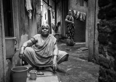 Indian lady sits on the ground, in the small streets of one of the slums in Pune, India. Streetphotography by Ellis Peeters