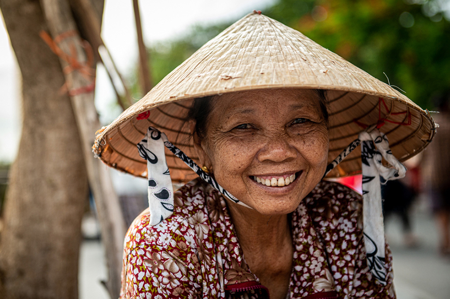 One of the many ladies that sells 'stuff' in the streets of Hoi An, Vietnam. She is wearing a typical Vietnamese straw hat. Travel portrait photography