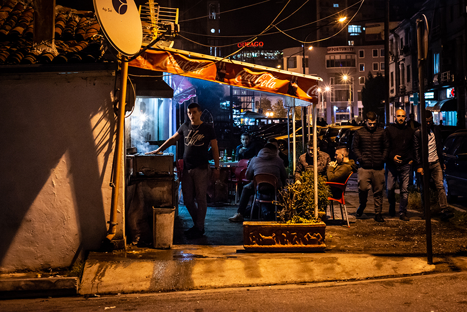 A street food seller bbq his food on the corner of the streets of Shkoder in Albania. Contrast in blue and yellow.