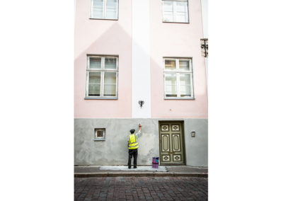 Work photography of a painter painting a house in the streets of Tallinn, Estonia. Seems to be an old man. Nice, soft lighting.
