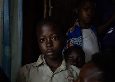 Travel portrait of a African boy in a dark living room. Rain drips are shown on his face. Ellis Photography.