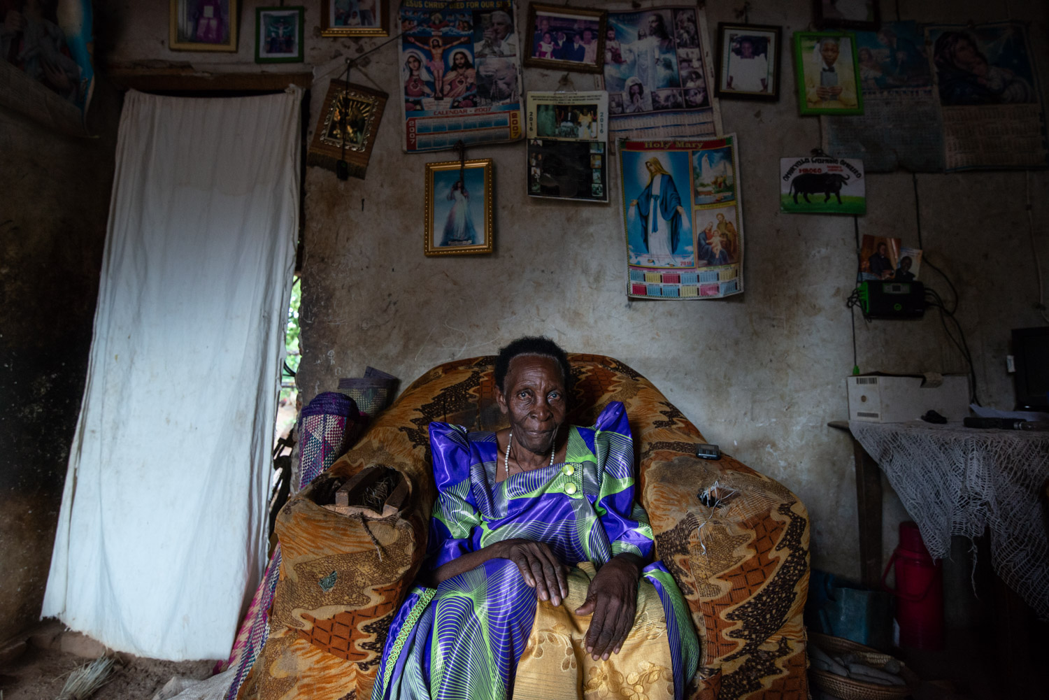 Portrait of an old woman in a remote rural village of Uganda. She sits in her chair in her dark living room. Above her hang many posters and photos. Made by Ellis Photography.
