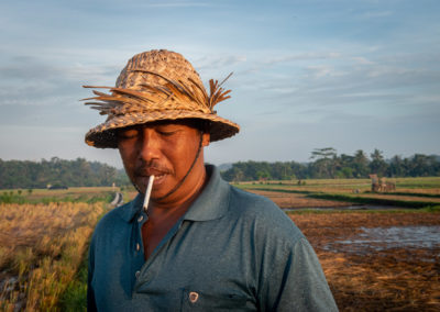 Portrait of a Balinese man smoking a sigaret during sunrise.